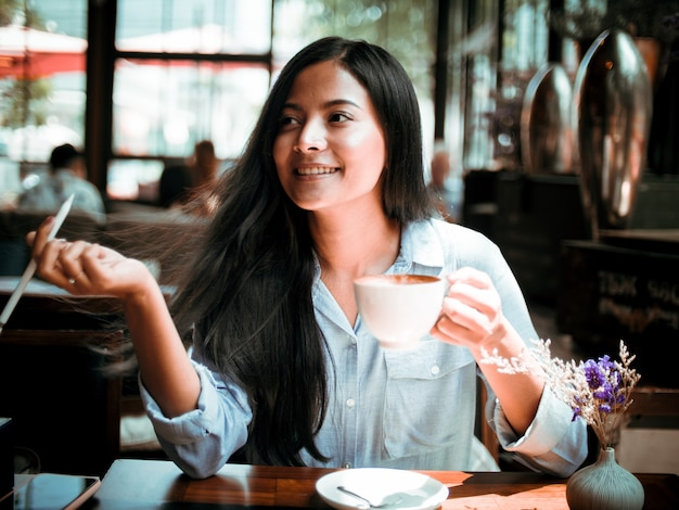 Asiatique femme buvant du café et travaillant avec ordinateur portable au café