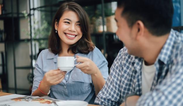 Asiatique femme en chemise bleue au café boire du café et parler avec son petit ami sourire et visage heureux