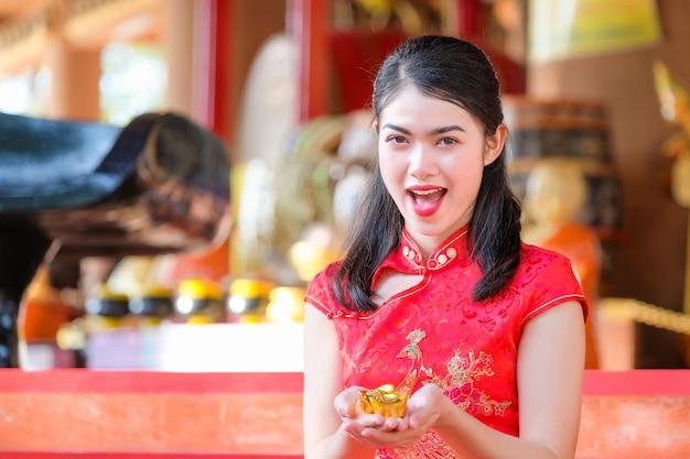 Asiatique femme chinoise traditionnelle chinoise détenir de l'argent chinois dans le temple chinois