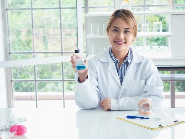 Asiatique femme dentiste montrant sur un modèle de mâchoire comment nettoyer les dents avec une brosse à dents