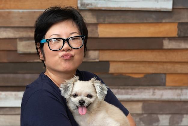 Asiatique femme étreignant le chien si mignon avec un mur en bois
