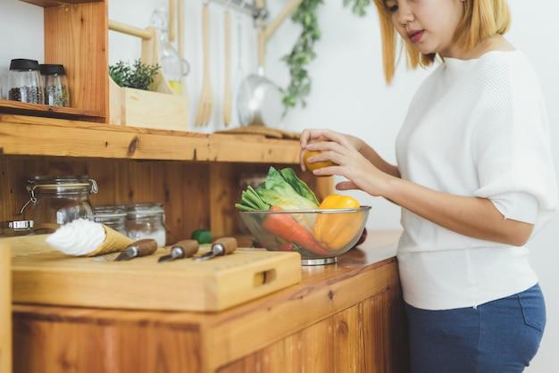 Asiatique, femme, faire, nourriture saine, debout, heureux, sourire, dans, cuisine, préparer