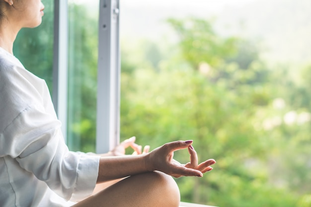 Asiatique femme faisant du yoga et méditant avec la nature