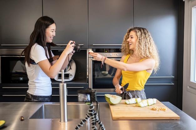 Asiatique femme filmant une femme caucasienne, coupe de fruits dans une cuisine.
