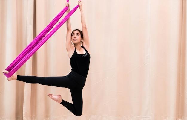 Asiatique femme formation en salle de fitness avec des éléments de yoga mouche