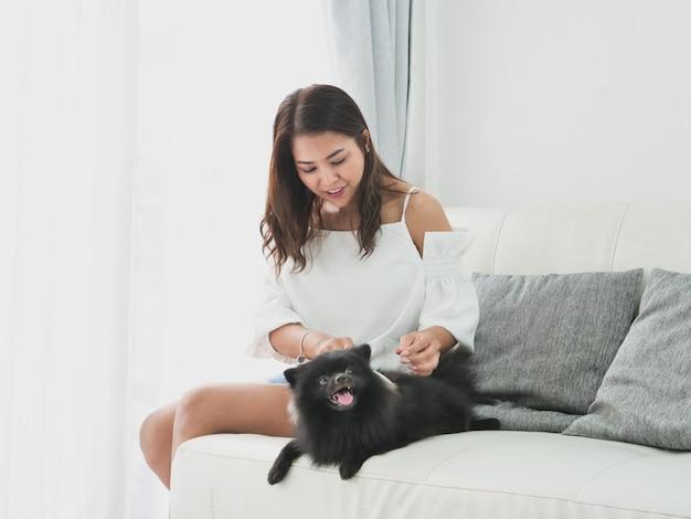 Asiatique, femme, jouer, à, petit chien, couleur noire, dans, salon, vie vie fille, à, animal de compagnie