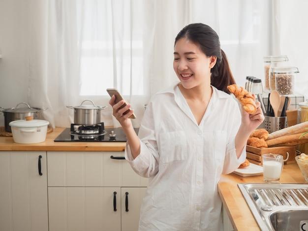 Asiatique, femme, manger pain, tout, utilisation, smartphone, dans cuisine