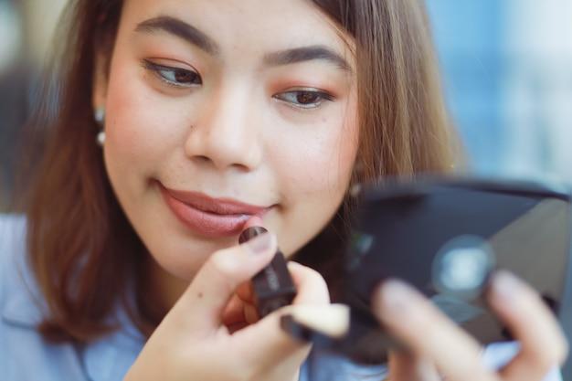 Asiatique femme maquiller son visage avec du rouge à lèvres au café