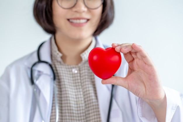 Asiatique femme médecin portant des lunettes tenez votre coeur souriant amicalement.