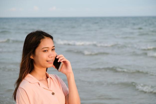 Asiatique femme parlant au téléphone portable debout sur la plage