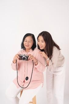 Asiatique femme plus âgée et sa fille sur mur blanc