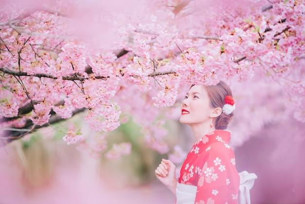 Asiatique femme portant un kimono avec des fleurs de cerisier, sakura au japon.