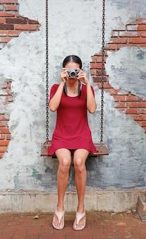 Asiatique femme prenant la caméra et assis sur la balançoire contre le vieux fond de mur de brique