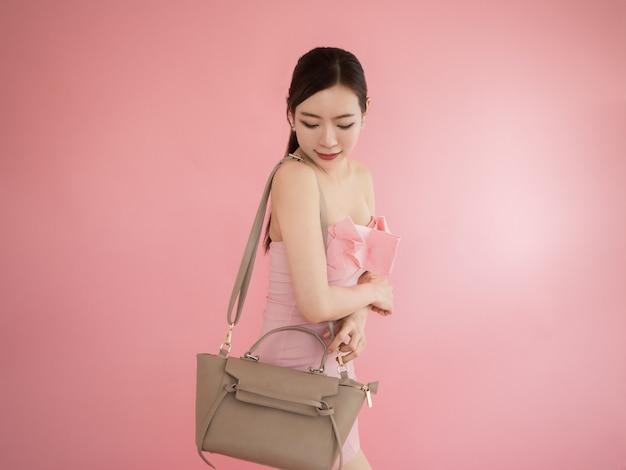 Asiatique femme à la recherche de sac à bandoulière, fille sexy show sac à main sur fond rose