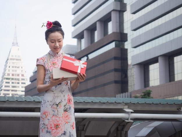 Asiatique femme en robe chinoise tenant une boîte cadeau rouge à la main avec fond de ville