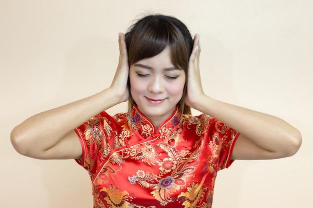 Asiatique femme saluant en chinois traditionnel ou cheongsam avec les mains