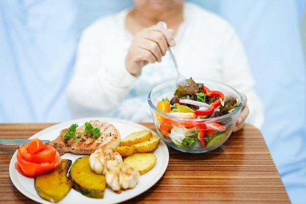 Asiatique femme senior patient déjeunant à l'hôpital.