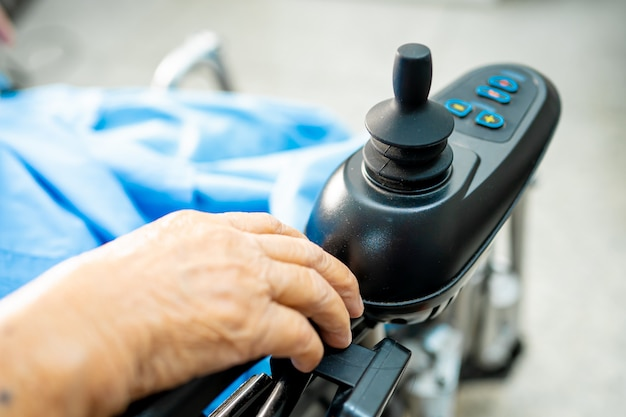 Asiatique femme senior patient sur fauteuil roulant électrique avec télécommande à l'hôpital.