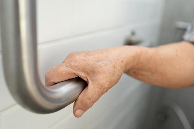 Asiatique femme senior patient utiliser toilettes salle de bain gérer la sécurité à l'hôpital.