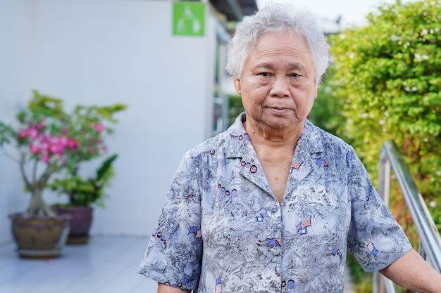 Asiatique femme senior sourire visage tout en marchant au parc en vacances.