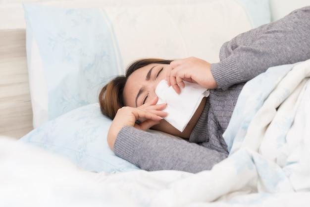 Asiatique femme souffrant de grippe et allongée sur le lit avec un tissu