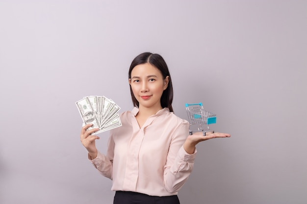 Asiatique femme tenant en argent et panier d'achat à la main