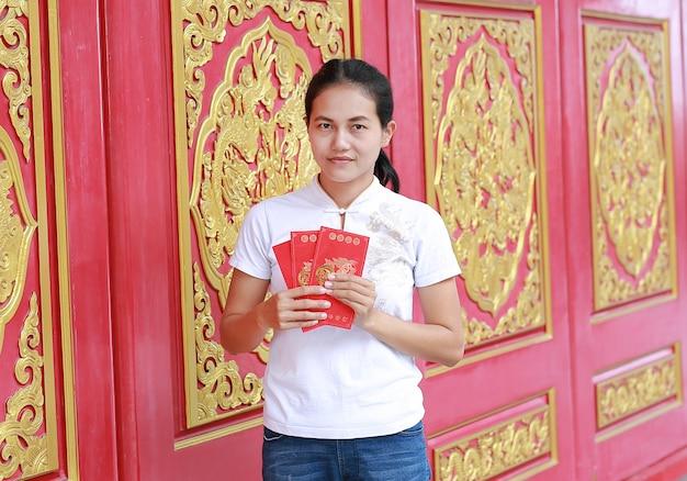 Asiatique femme tenant un cadeau monétaire paquet rouge au temple chinois à bangkok, thaïlande.