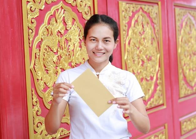Asiatique femme tenant un paquet d'argent cadeau monétaire au temple chinois à bangkok, thaïlande.