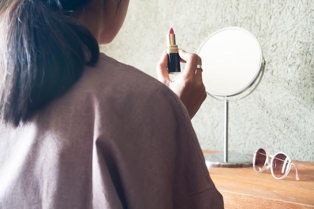 Asiatique femme tenant le rouge à lèvres prépare le maquillage pour sortir. concept de beauté et de style de vie