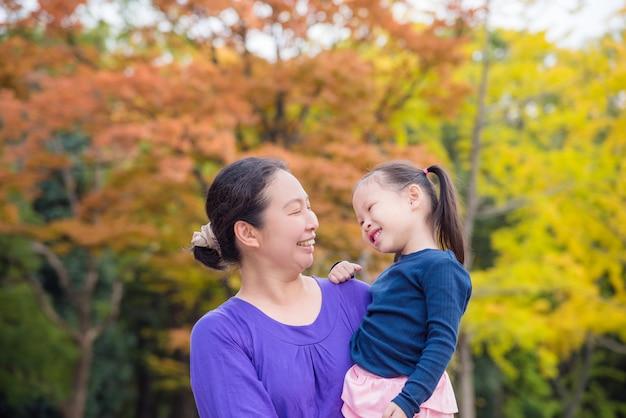 Asiatique femme tenant sa fille et souriant ensemble en automne parc