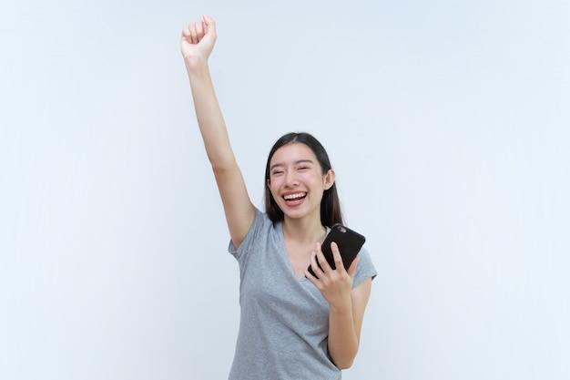 Asiatique femme tenant un smartphone, belle jeune femme heureuse de remporter la victoire