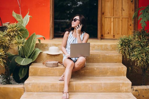 Asiatique femme travaillant sur un ordinateur portable en vacances et assis dans les escaliers