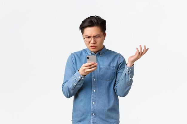 Un asiatique frustré et confus dans des lunettes, l'air perplexe devant l'écran du téléphone portable, levant la main interrogé, ne peut pas comprendre ce qui se passe en ligne, debout sur fond blanc perplexe