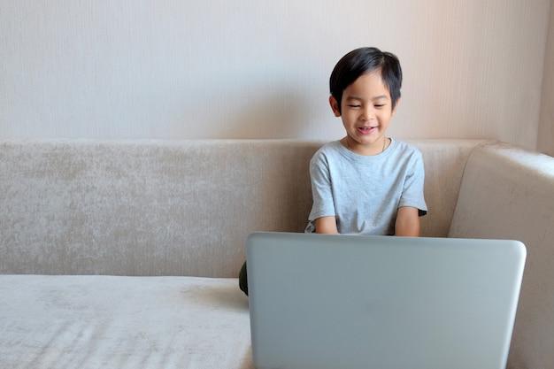 Asiatique garçon enfant assis sur un canapé et utilise un ordinateur portable pour l'éducation