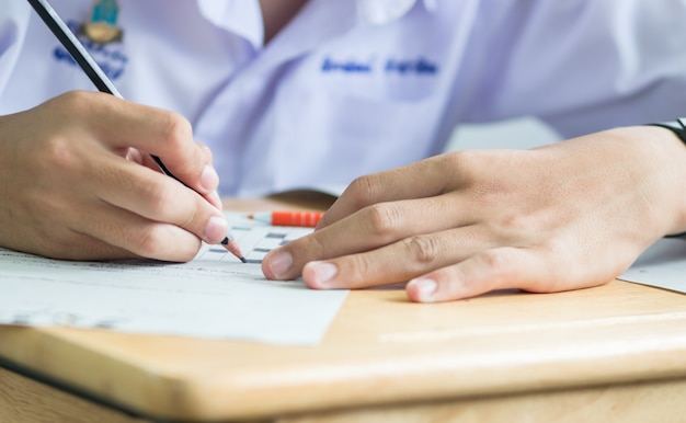 Asiatique garçon étudiants prenant des examens, écrit la salle d'examen