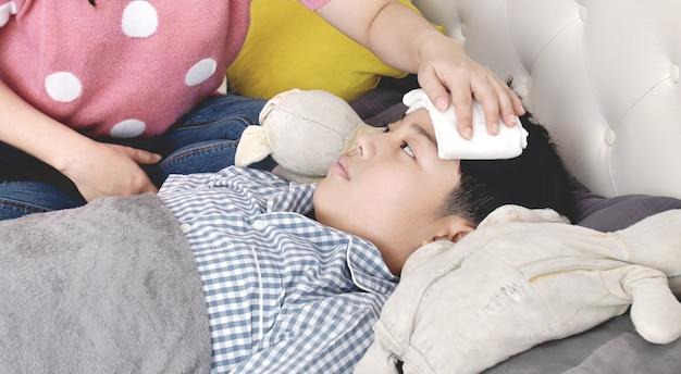 Asiatique garçon malade, couché dans son lit, sa mère vérifiant sa température,