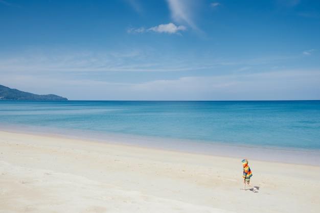 Asiatique garçon marchant sur la plage en plein air mer et ciel bleu