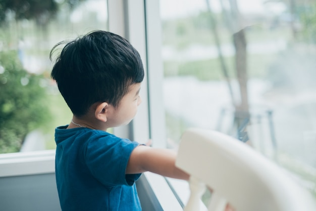 Asiatique garçon regardant par la fenêtre