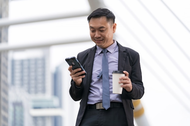 Asiatique homme d'affaires debout et tenant un téléphone portable