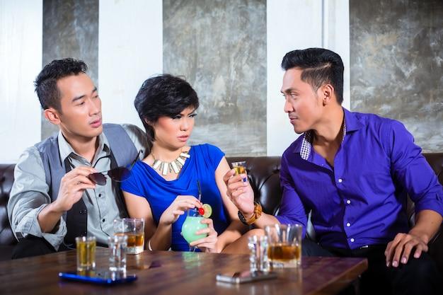 Asiatique homme harcelant une femme dans une discothèque chic