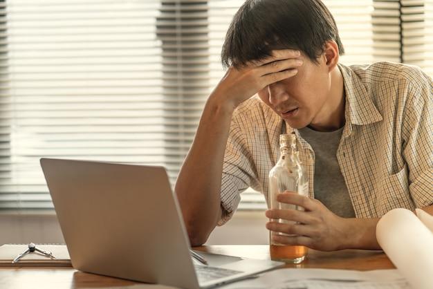 Asiatique ingénieur en affaires, maux de tête, stressé par des problèmes d'erreur de travail et de perte de profit, risque d'être licencié de son travail