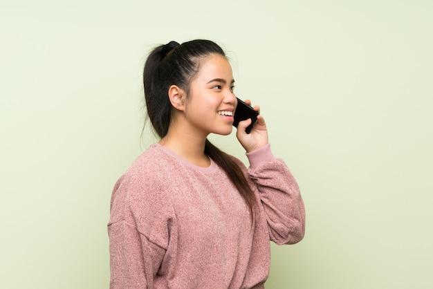 Asiatique jeune adolescente sur mur vert isolé à l'aide de téléphone portable