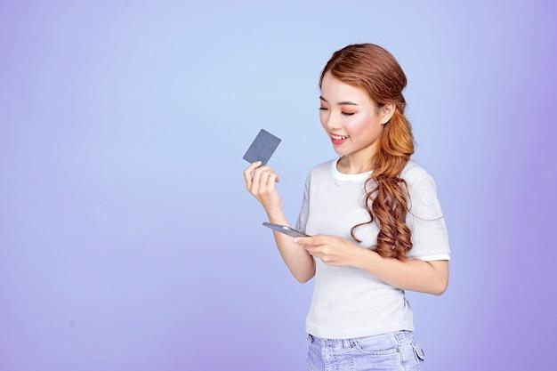 Asiatique jeune belle jolie jolie étudiante tenant une carte de crédit et un téléphone intelligent