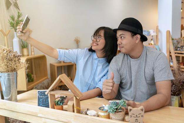 Asiatique jeune couple prenant le selfie avec une action de bonheur dans un café moderne