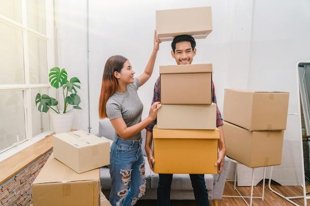 Asiatique jeune couple transportant une grosse boîte en carton pour se déplacer