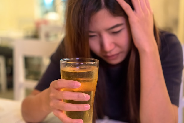 Asiatique jeune femme en action solitaire et déprimée et tenant un verre de bière dans un pub et reste