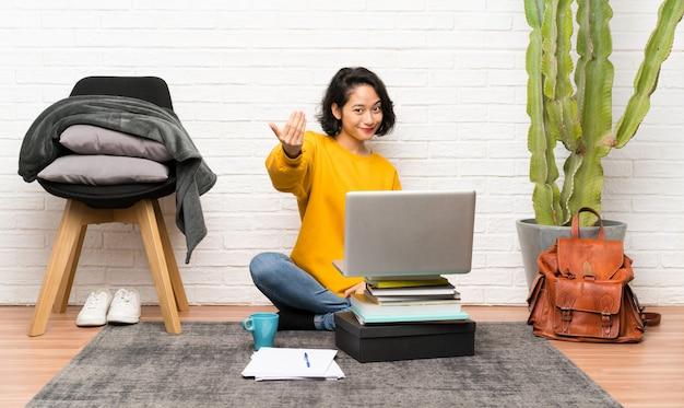 Asiatique jeune femme assise sur le sol invitant à venir