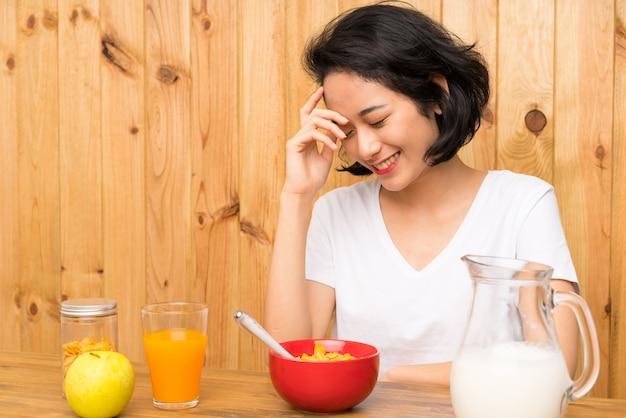Asiatique, jeune femme, avoir petit déjeuner lait, rire