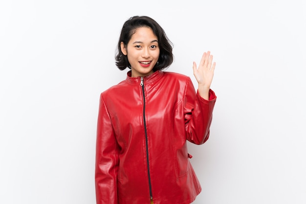 Asiatique jeune femme sur blanc isolé, saluant avec la main avec une expression heureuse