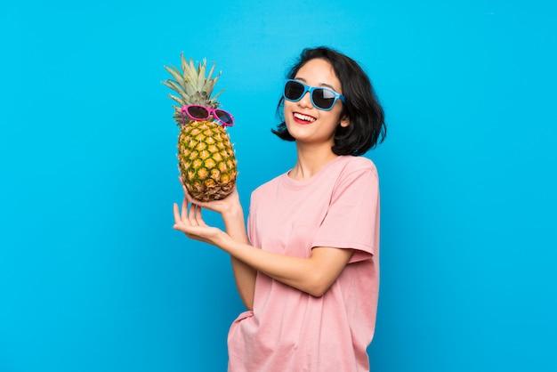 Asiatique jeune femme sur bleu isolé, tenant un ananas avec des lunettes de soleil